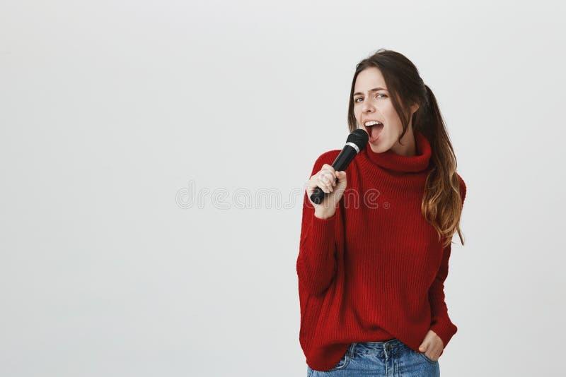 Porträt des stilvollen schönen Mädchens, das im Karaoke, Mikrofon halten, tragende nette rote Winterstrickjacke über Weiß singt stockbild