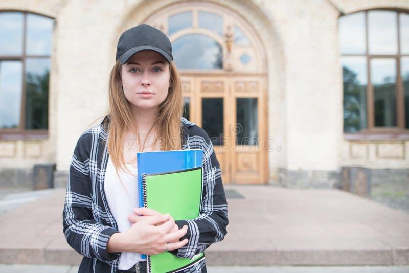 Porträt des Studentenmädchens in der zufälligen Kleidung, die auf Hintergrund des Hochschulgebäudes steht und Kamera betrachtet stockfotos