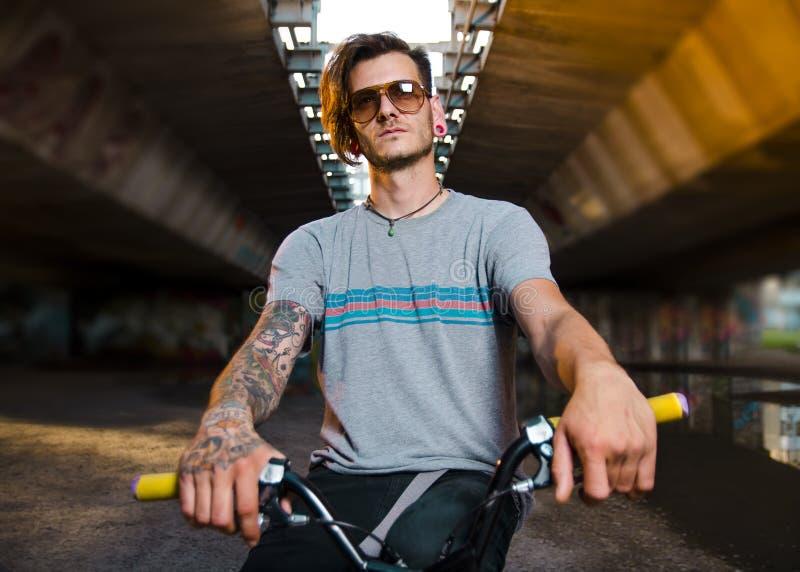 Porträt des tätowierten jungen erwachsenen Mannes auf BMX-Fahrrad lizenzfreies stockbild