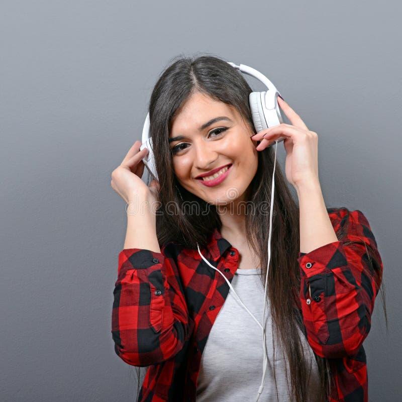 Porträt des Tanzens der städtischen Frau mit Kopfhörern gegen grauen Hintergrund stockfotos