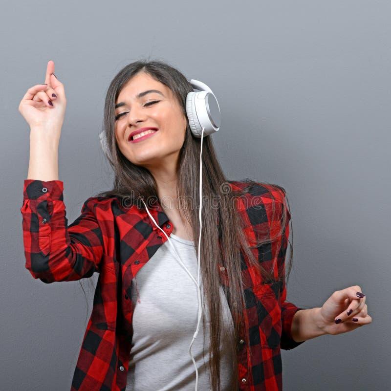 Porträt des Tanzens der städtischen Frau mit Kopfhörern gegen grauen Hintergrund lizenzfreies stockfoto