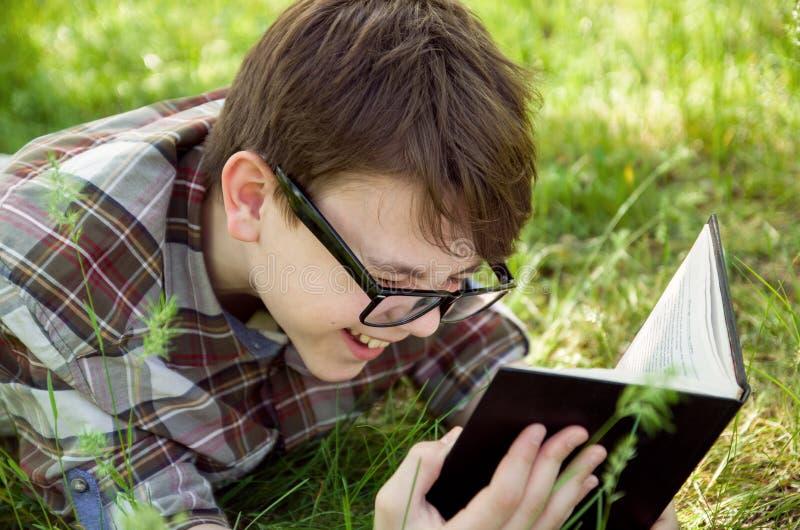 Porträt des Teenagerabschlusses oben Junge mit dem Glaslesebuch und -c$lachen Glückliches Wochenende Park, im Freien stockfotografie