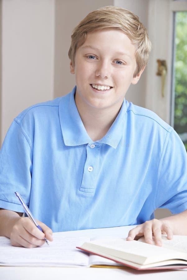Porträt des Teenagers Hausarbeit bei Tisch tuend stockfotos