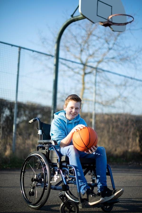 Porträt des Teenagers im Rollstuhl, der Basketball auf Gericht im Freien spielt lizenzfreies stockbild