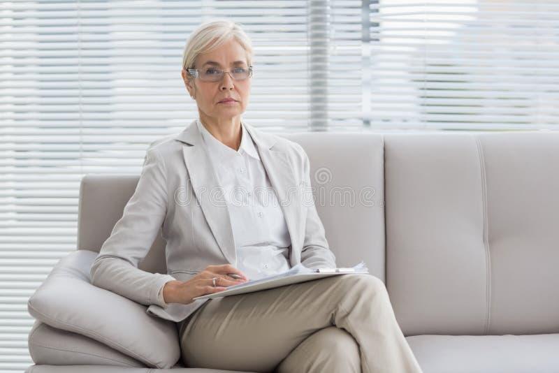 Porträt des Therapeuten sitzend auf Sofa lizenzfreie stockfotos