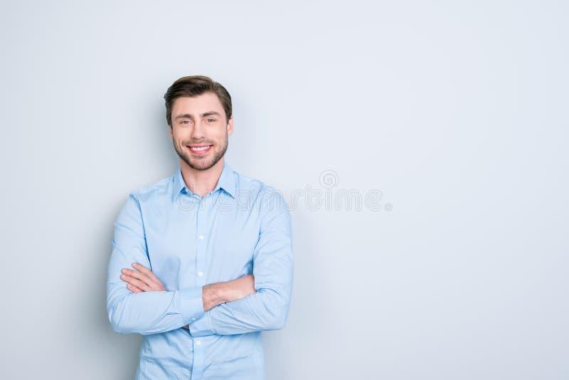 Porträt des toothy hübschen bärtigen Managers mit gekreuzten Händen O lizenzfreie stockfotos