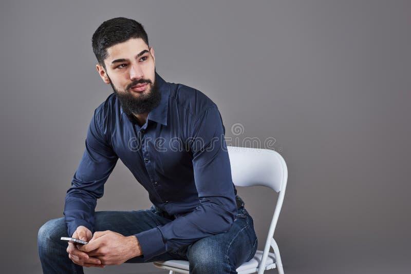 Porträt des toothy hübschen bärtigen Mannes, der auf einem Stuhl mit Telefon auf Händen sitzt lizenzfreies stockbild