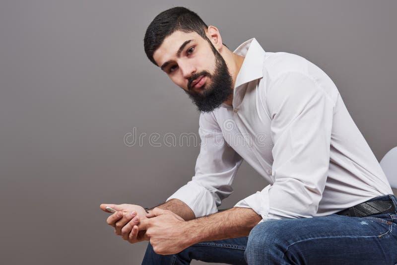 Porträt des toothy hübschen bärtigen Mannes, der auf einem Stuhl mit Telefon auf Händen sitzt stockbild