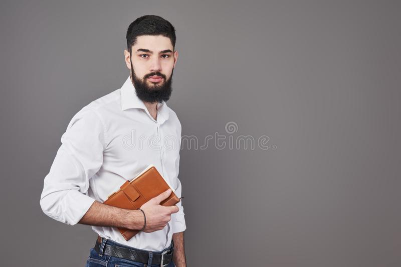 Porträt des toothy hübschen bärtigen Mannes mit Buch auf Händen stockfotos