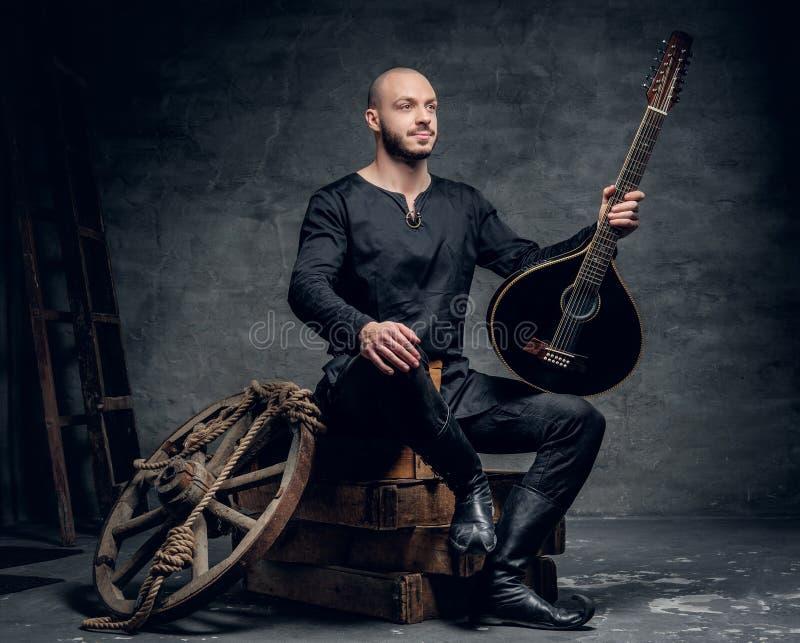 Porträt des traditionellen Volksmusikers, der in der keltischen Kleidung der Weinlese gekleidet wird, sitzt auf einer Holzkiste u stockbild