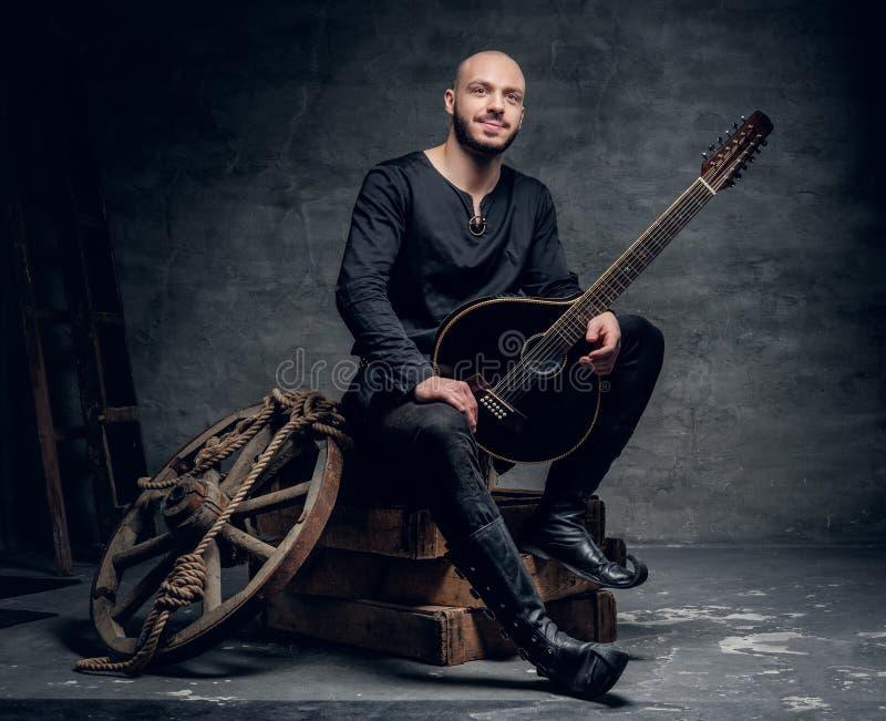 Porträt des traditionellen Volksmusikers, der in der keltischen Kleidung der Weinlese gekleidet wird, sitzt auf einer Holzkiste u lizenzfreies stockfoto