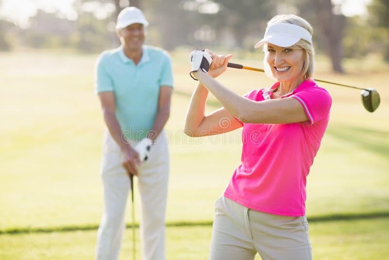 Porträt des tragenden Golfclubs der überzeugten reifen Frau durch Mann stockfotos