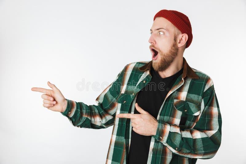 Porträt des tragenden Hutes und des karierten Hemds des jungen unshaved Mannes, die, beim Zeigen von den Fingern beiseite lokalis stockfoto