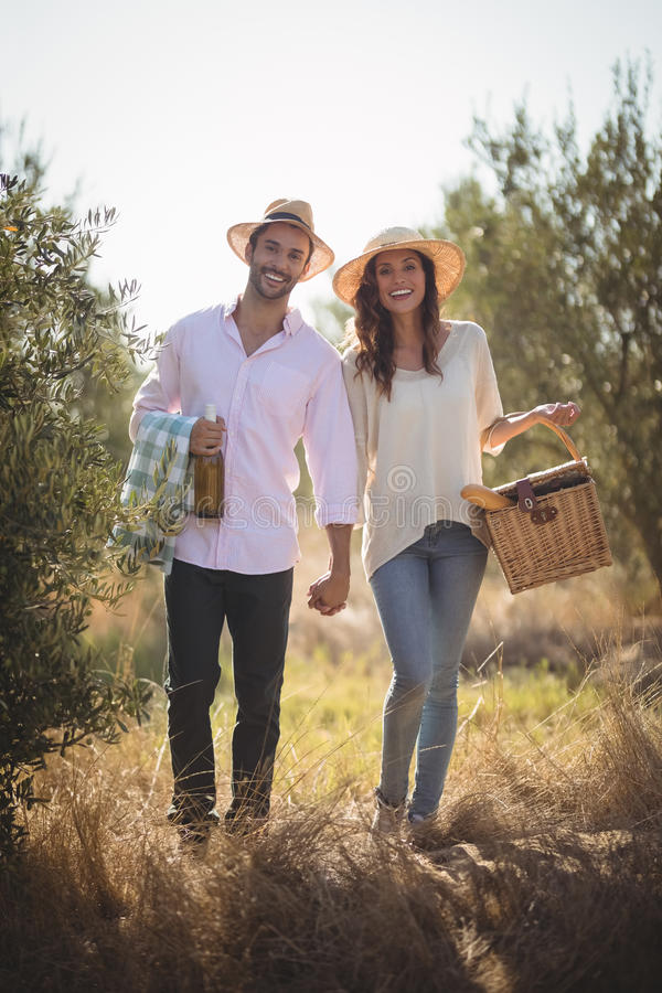 Porträt des tragenden Picknickkorbes der glücklichen jungen Paare lizenzfreies stockfoto