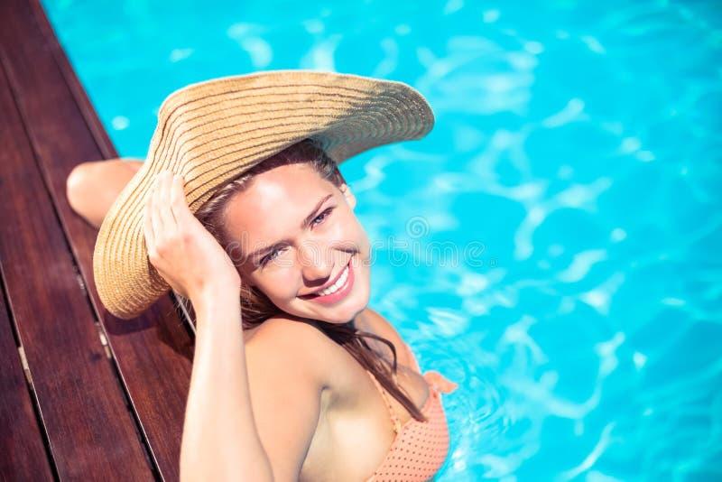Porträt des tragenden Strohhutes der Frau, der auf hölzerner Plattform durch Poolside sich lehnt lizenzfreie stockfotos