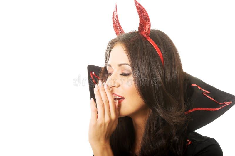 Porträt des tragenden Teufels der Frau kleidet das Flüstern zu jemand stockbild