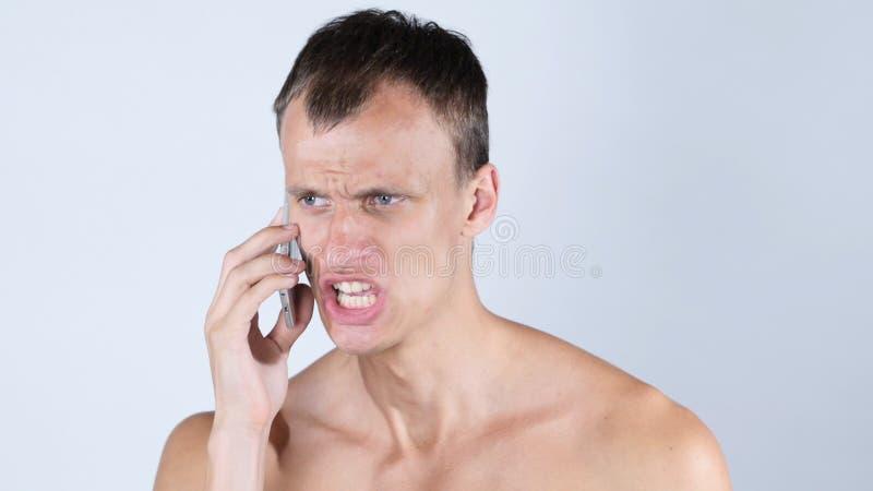Porträt des traurigen hoffnungslosen verärgerten Mannes, der auf Telefon und dem Schreien spricht stockbild