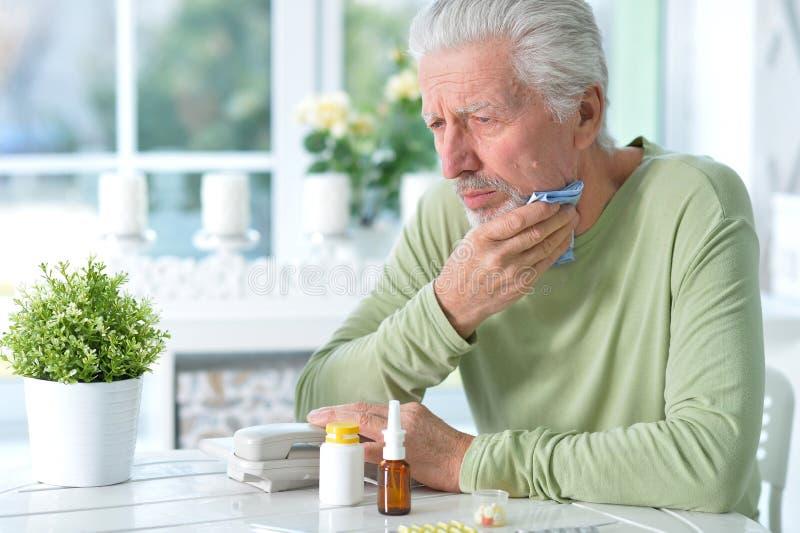 Porträt des traurigen kranken älteren Mannes zu Hause stockbild