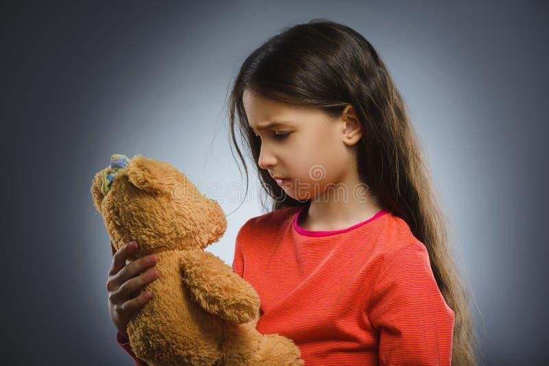 Porträt des traurigen oder unglücklichen Mädchens, das mit dem Teddybären lokalisiert auf Grau spielt lizenzfreie stockfotografie