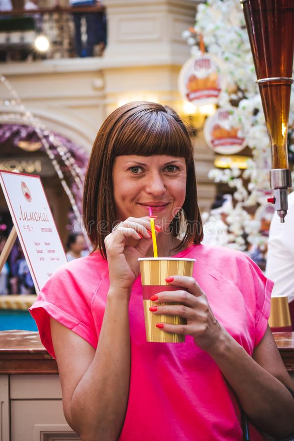 Porträt des trinkenden Sodas der jungen Frau am Einkaufszentrum stockbild