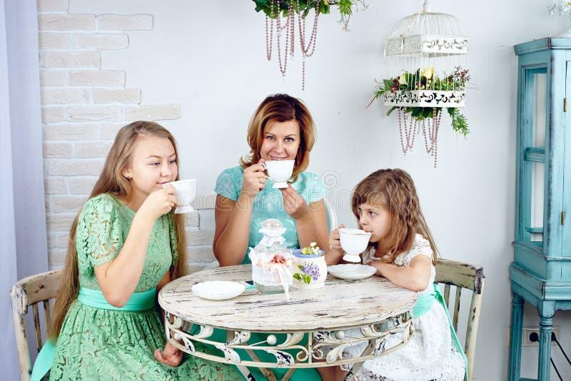 Porträt des trinkenden Tees der glücklichen Mutter mit ihren zwei Töchtern stockbild