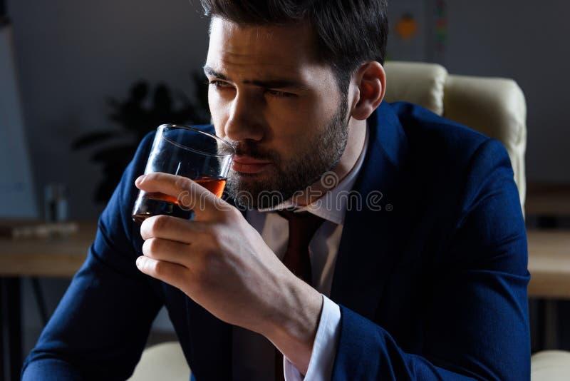 Porträt des trinkenden Whiskys des Geschäftsmannes lizenzfreies stockbild