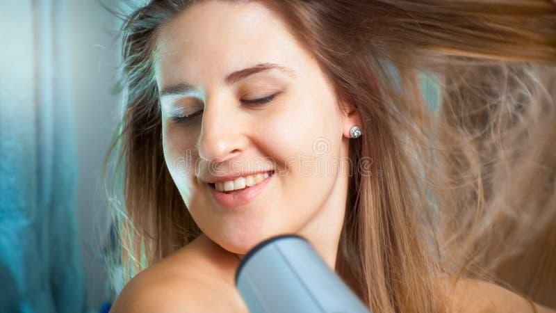 Porträt des trocknenden Haares der schönen Brunettefrau im Badezimmer lizenzfreie stockfotos