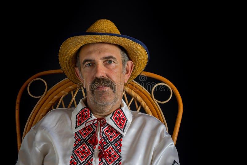Porträt des ukrainischen Landsmannes sitzend in einem geflochtenen Stuhl stockbilder