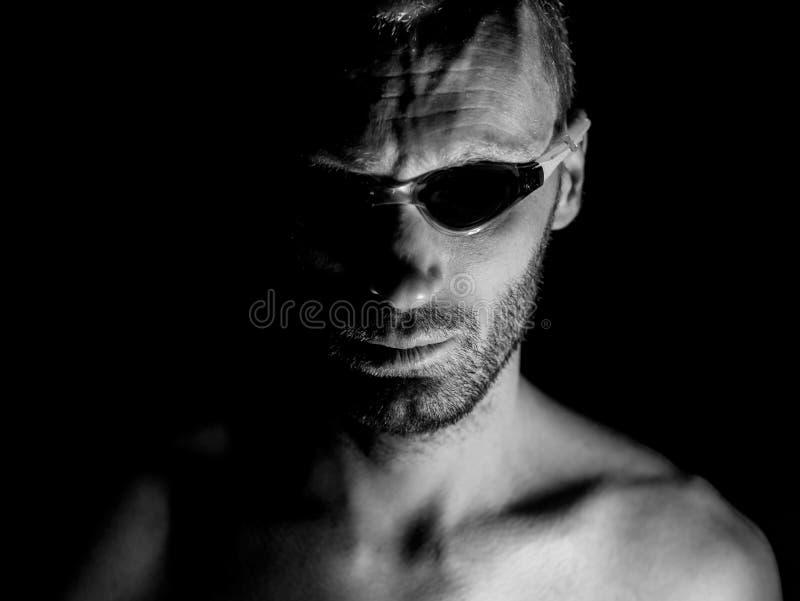 Porträt des unrasierten erwachsenen kaukasischen Mannes in schwimmenden Gläsern Er schaut gerade zum Beobachter Schwarzweißaufnah stockbilder