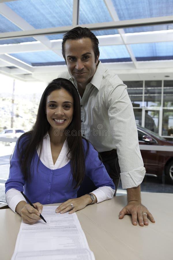 Porträt des unterzeichnenden Autovertrages der Frau mit dem Ehemann, der hinten steht stockfoto