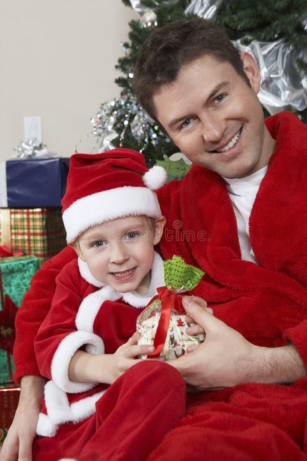 Porträt des Vaters And Son In Santa Claus Outfit Holding Present lizenzfreie stockfotos
