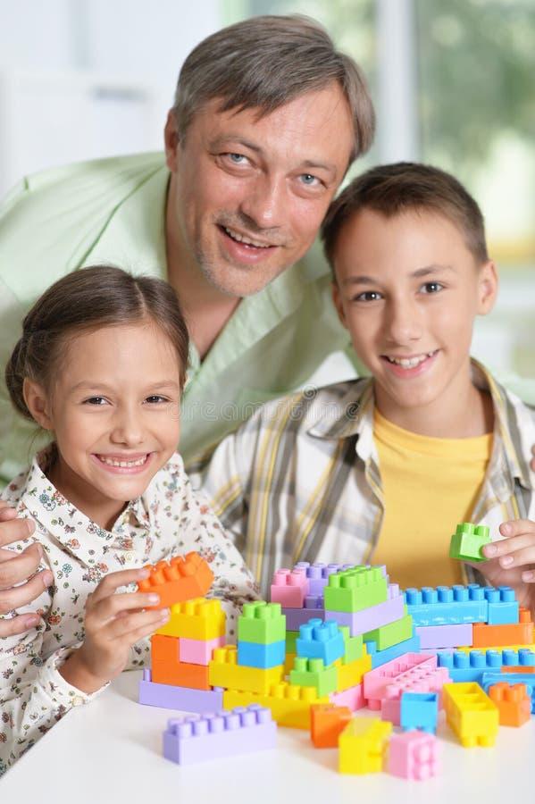 Porträt des Vaters und der Kinder, die mit bunter Plastikquerstation spielen lizenzfreie stockfotografie