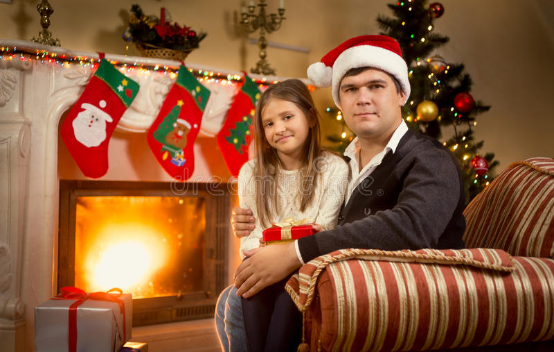 Porträt des Vaters und der Tochter, die auf Stuhl am Kamin sitzen stockfoto