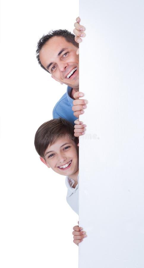 Porträt des Vaters und des Jungen hinter leerem Brett stockfotos