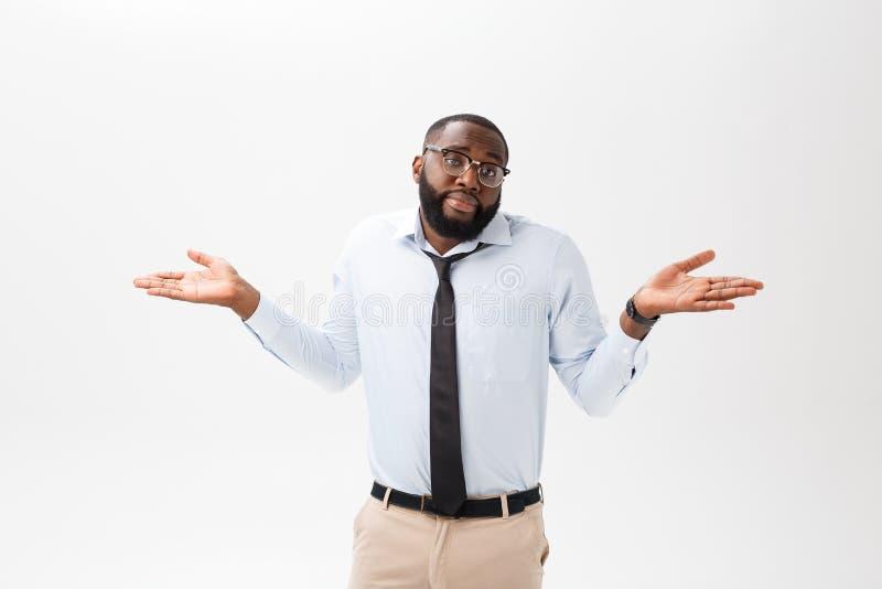 Porträt des verärgerten oder gestörten jungen Afroamerikanermannes im weißen Polohemd, welches die Kamera mit missfallen betracht stockfoto