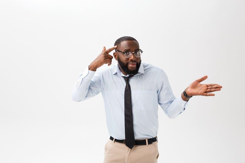 Porträt des verärgerten oder gestörten jungen Afroamerikanermannes im weißen Polohemd, welches die Kamera mit missfallen betracht stockbilder