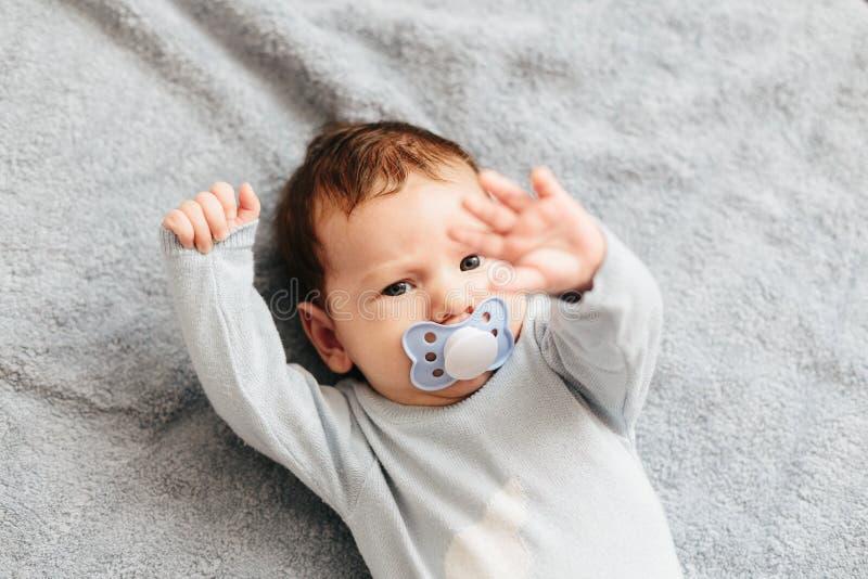 Porträt des verärgerten, wütenden, die Stirn runzelnden und aggressiven Lügens des Babys auf einem Bett Die Gef stockfotos
