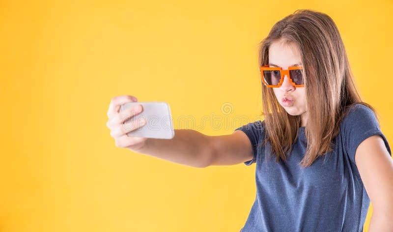 Porträt des verrückten jugendlich Mädchens mit den Retro- Gläsern, die selfie über gelbem Hintergrund machen lizenzfreie stockfotografie