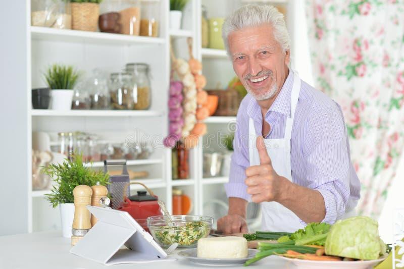 Porträt des Vertretungsdaumens des älteren Mannes oben beim Vorbereiten des Abendessens in der Küche lizenzfreie stockfotografie