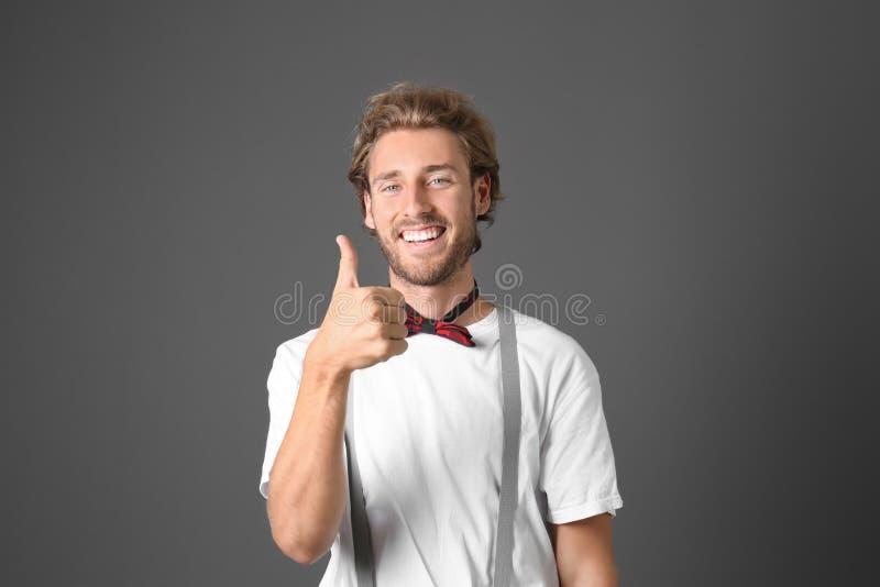 Porträt des Vertretungsdaumens-oben des gut aussehenden Mannes auf grauem Hintergrund lizenzfreie stockfotografie