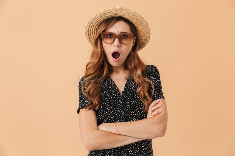Porträt des verwirrten entsetzten tragenden Strohhutes und der Sonne der Frau 20s lizenzfreies stockfoto