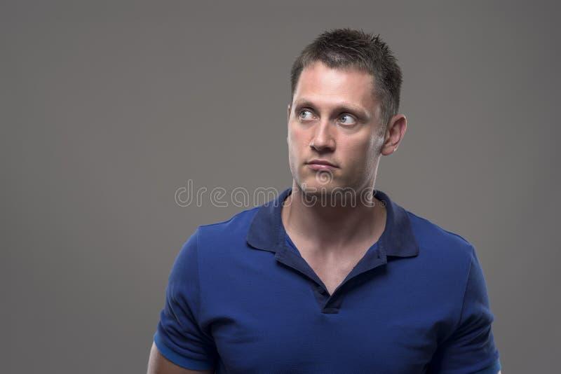 Porträt des verwirrten jungen erwachsenen Mannes, der oben Kopienraum betrachtet lizenzfreie stockfotografie