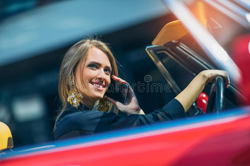 Porträt des vorbildlichen Sitzens der schönen sexy Modefrau im Luxusauto stockbilder
