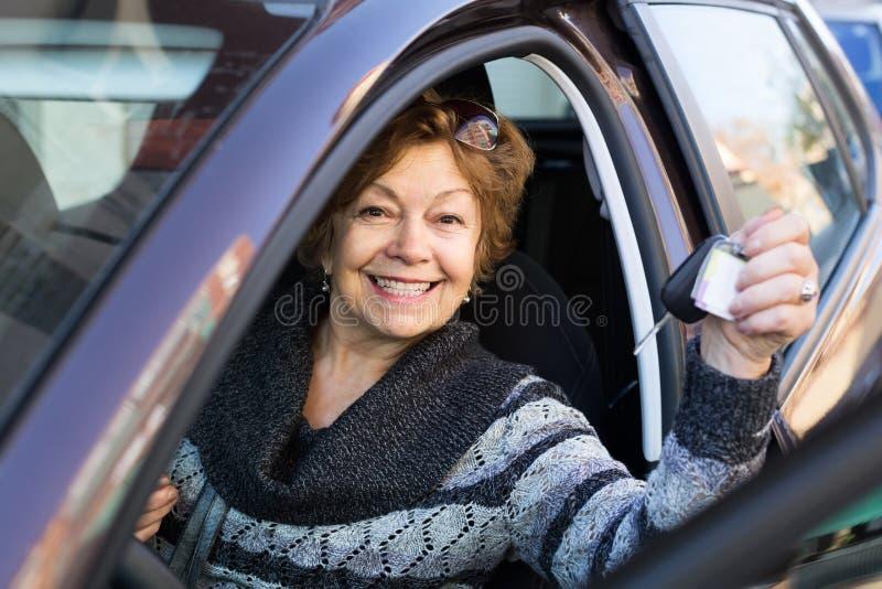 Porträt des weiblichen älteren Fahrers im Auto stockbild
