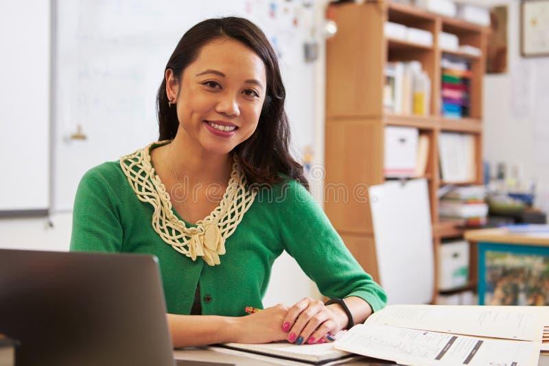 Porträt des weiblichen asiatischen Lehrers an ihrem Schreibtisch lizenzfreie stockfotos
