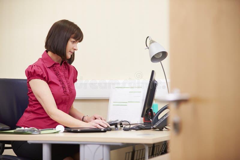 Porträt des weiblichen Beraters Working At Desk im Büro lizenzfreie stockfotografie
