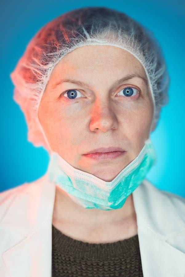 Porträt des weiblichen Chirurgen schützende chirurgische Maske tragend lizenzfreie stockfotografie