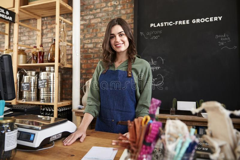 Porträt des weiblichen Inhabers des stützbaren freien PlastikGemischtwarenladens hinter Verkaufs-Schreibtisch lizenzfreie stockfotografie