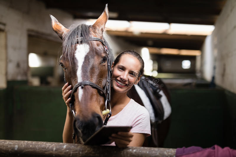 Porträt des weiblichen Jockeys Tablet-Computer beim Bereitstehen des Pferds halten stockfoto