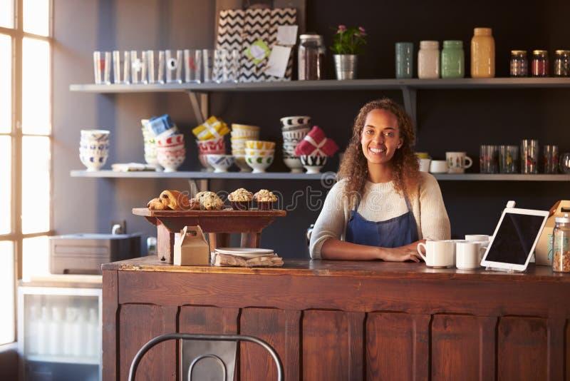 Porträt des weiblichen Kaffeestube-Inhabers, der hinter Zähler steht lizenzfreies stockfoto